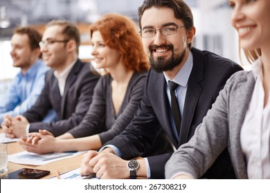 Young businessman sitting among co-workers and looking at camera at conference