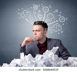 Young businessman sitting behind crumpled paper with drawings of gears and steam over his head