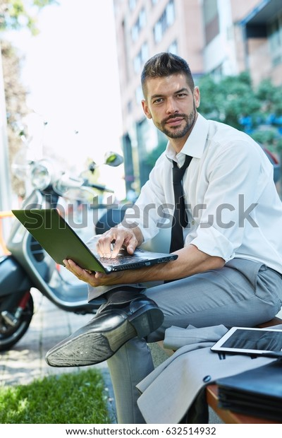 Young businessman sitting brench outdoors in front of office building using laptop.