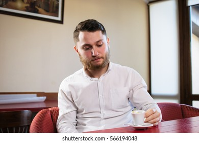 Young businessman sitting in cafe and taking a cup of coffee