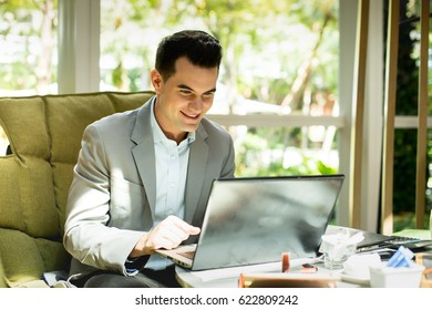 Young businessman sitting in cafe while using laptop computer.Business people using laptop for conference call.