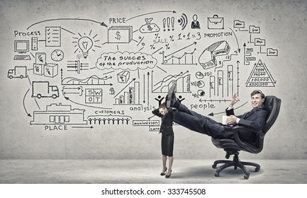 Young businessman sitting in chair with legs on colleagues shoulders