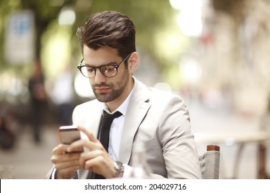 Young businessman sitting in coffee shop while using his mobile. Small business.