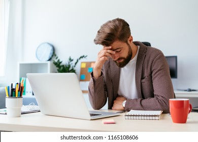 Young businessman sitting at desk and having headache while working with laptop in modern office