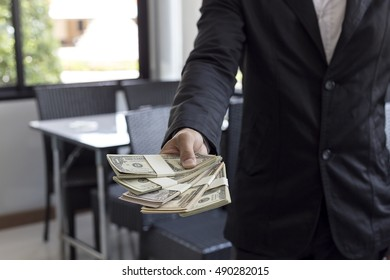 Young businessman sitting at a desk in the office. Counting money for investment decisions.