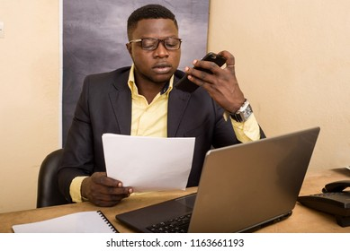 young businessman sitting at desk working on laptop talking on the phone