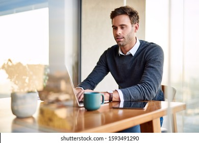 Young businessman sitting at a dining room table and using a laptop while working from home