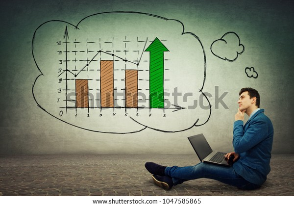 Young businessman sitting down on floor using laptop imagine a rising graph of virtual sales, crypto currency financial business development. Chart shows profit and growth of virtual money.