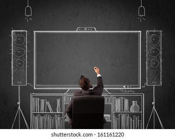 Young businessman sitting and enjoying home cinema system sketched on a chalkboard