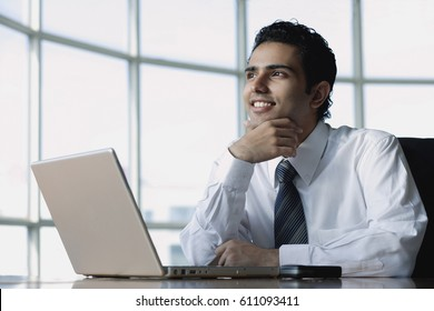 Young businessman sitting in front of laptop, smiling, looking away
