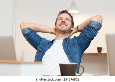 Young businessman sitting with hands behind head in office