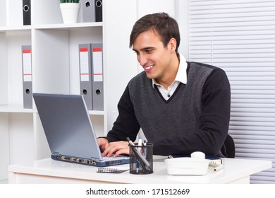 Young businessman sitting in his office and working on his laptop,Businessman using laptop