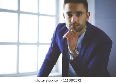 Young businessman sitting isolated on grey background