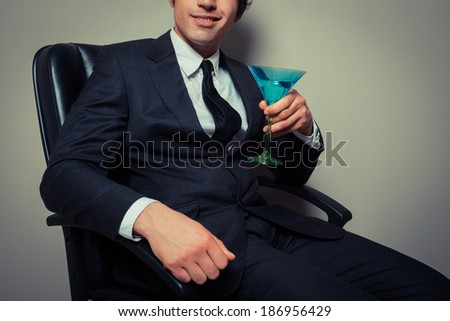 Young businessman sitting in an office chair with a cocktail