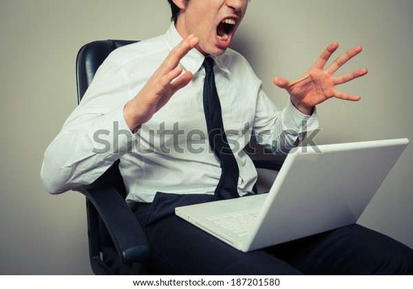 Young businessman sitting in office chair is angry at his laptop