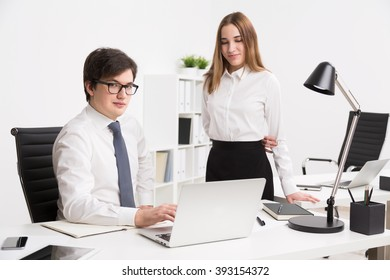 Young businessman sitting at office table, cunningly looking in camera. Young businesswoman standing next to him. Concept of office work.