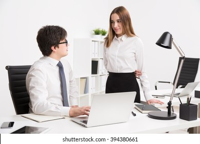 Young businessman sitting at office table and talking  to young businesswoman standing next to him. Concept of office work.