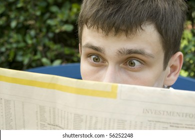Young businessman sitting on a bench outside the premises read a newspaper. Express emotions of shock, surprise