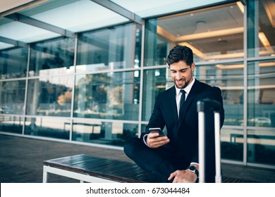 Young businessman sitting on bench with suitcase and using smart phone. Caucasian businessman waiting at airport terminal holding mobile phone.