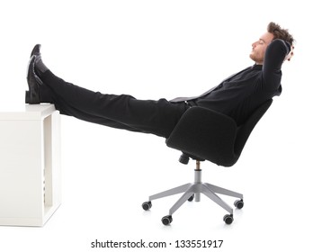 Young businessman sitting on chair, resting with legs on desk, eyes closed.
