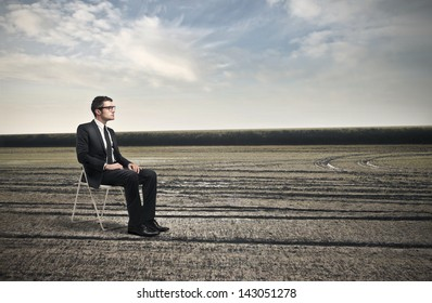 young businessman sitting on a chair in the countryside