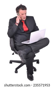 Young businessman is sitting on the chair and talking on his smartphone and checking email