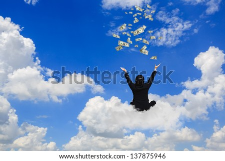 Young businessman sitting on the cloud with a lot of falling dollars