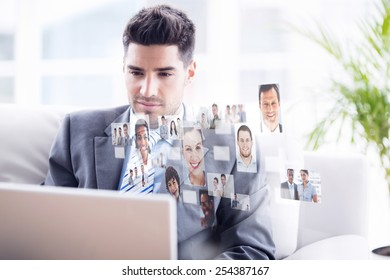 Young businessman sitting on couch using his laptop against business people