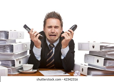 Young businessman is sitting on desk, holding two telephones and crying because of unmanageable work. Isolated on white.