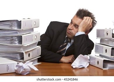 Young businessman is sitting on desk and looks frustrated on folder stack , becuase of unmanageable work. Isolated on white.