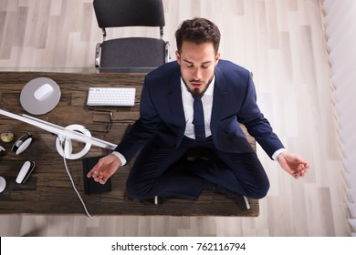 Young Businessman Sitting On Desk Doing Yoga In Office