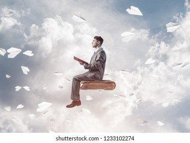 Young businessman sitting on floating in air book with one in hands