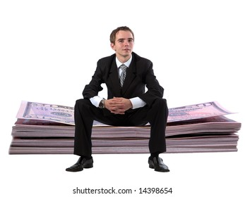 Young businessman sitting on huge dollar stack
