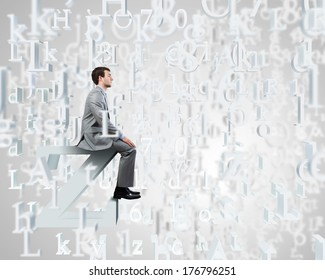 Young businessman sitting on huge white letter. Email concept
