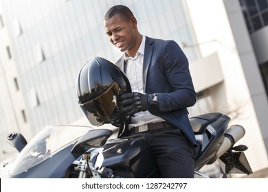 Young businessman sitting on motorcycle holding helmet smiling cheerful ready to go
