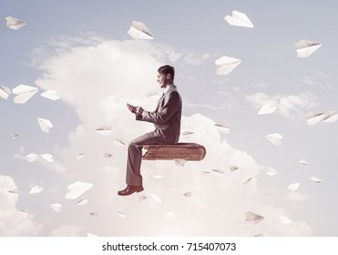 Young businessman sitting on old book with mobile phone in hands