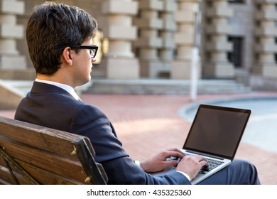 Young businessman sitting on outdoor bench and using laptop with blank screen. Mock up