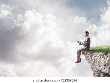 Young businessman sitting on rock with smartphone in hands