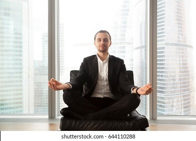 Young businessman sitting in soft chair in lotus position. Calm man in business suit meditating on couch with crossed legs. Entrepreneur engage in spiritual practices for mental health, stress relief