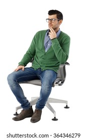 Young businessman sitting in swivel chair over white background, looking away, thinking. Full size.