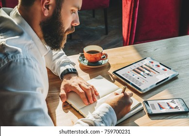 Young businessman is sitting at table and making notes in notebook.On table is tablet computer,smartphone with graphs, charts, diagrams on screen, cup of coffee.Online marketing,education, e-learning.