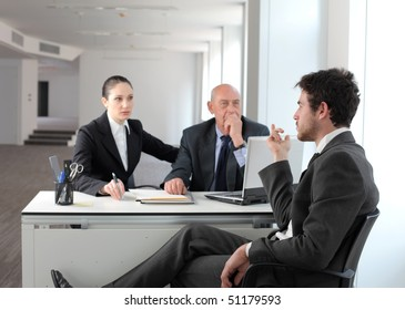 Young businessman sitting and talking to other business people