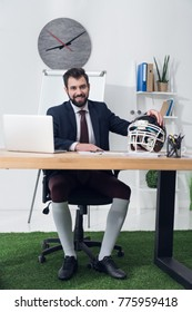 young businessman sitting at workplace with rugby helmet in office