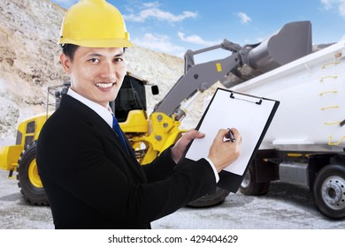 Young businessman smiling at the camera while writes on a clipboard with mining vehicle at mining site