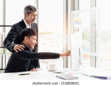 The young businessman smiling and checking the point to the screen. He is discussing with his boss on the desk in his office room.