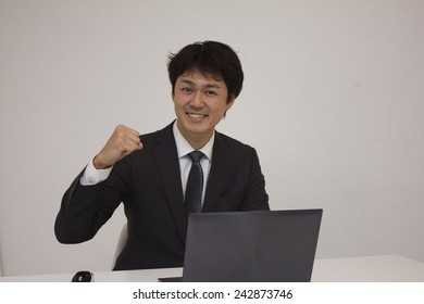 Young businessman smiling with his fist up