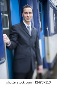 Young businessman smiling at train doorway