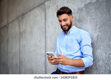 Young businessman smiling while texting on smartphone in the city
