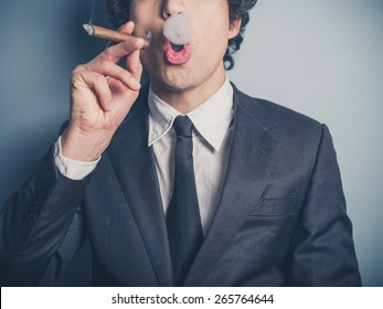 A young businessman is smoking a cigar and is blowing smoke rings