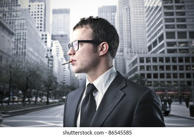 Young businessman smoking a cigarette on a city street